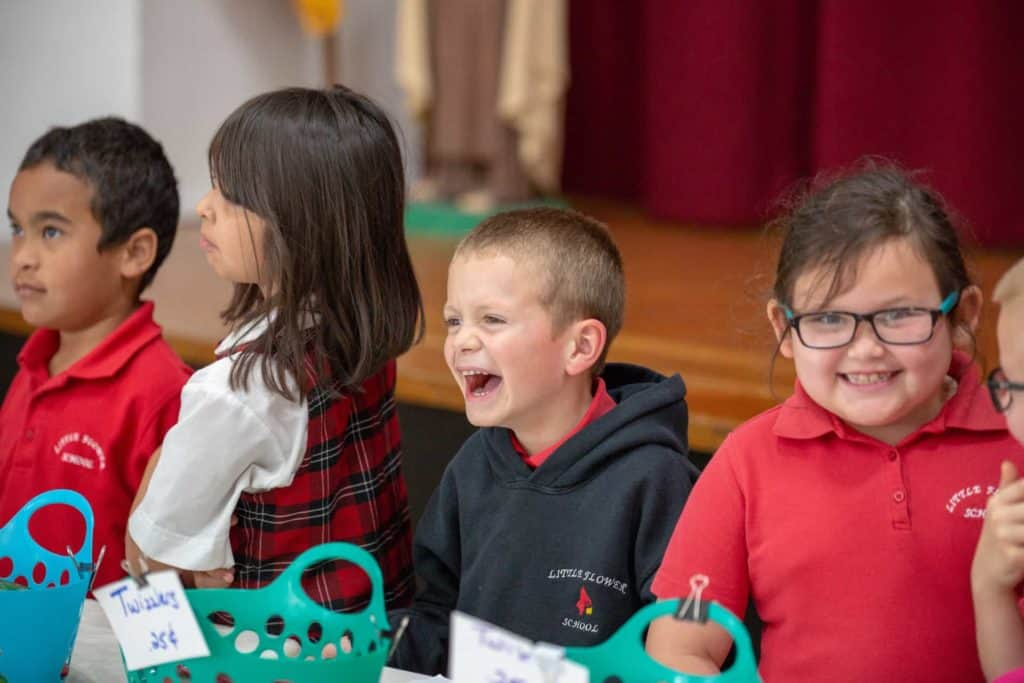 A young student laughing with great joy during a bake sale at Little Flower Catholic School