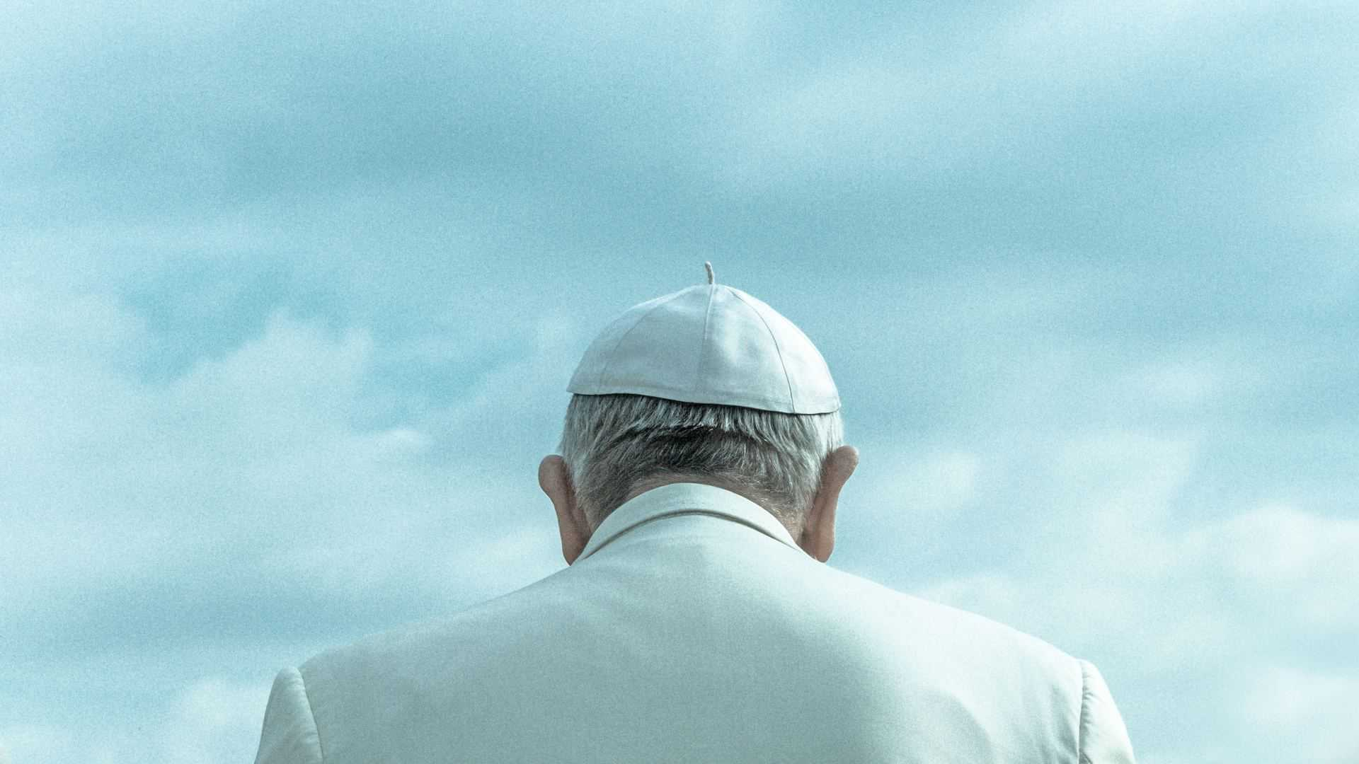 The back of Pope Francis against a blue cloudy sky
