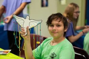 Kid holding up a craft at Vacation Bible School 2018 at Little Flower Catholic Church