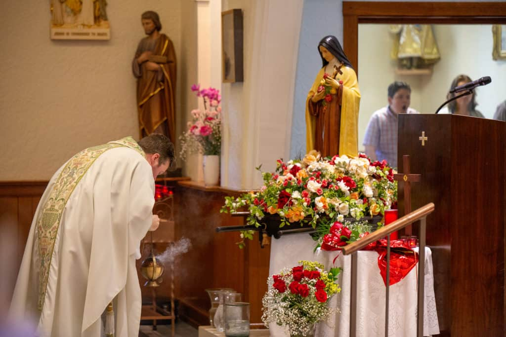Reverencing statue for St. Therese of Lisieux before Mass at Little Flower Catholic Church