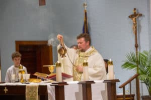 Fr. Matt Worthen incensing above the gifts on the altar at Mass at Little Flower Catholic Church