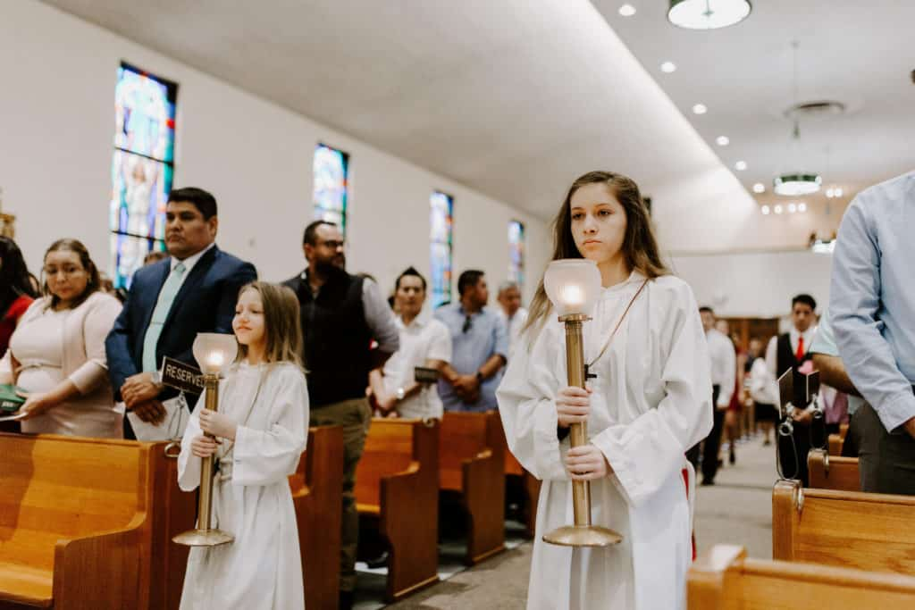 Two altar servers wearing white albs and holding candles process into Mass at the 2019 Confirmation Mass at Little Flower Catholic Church
