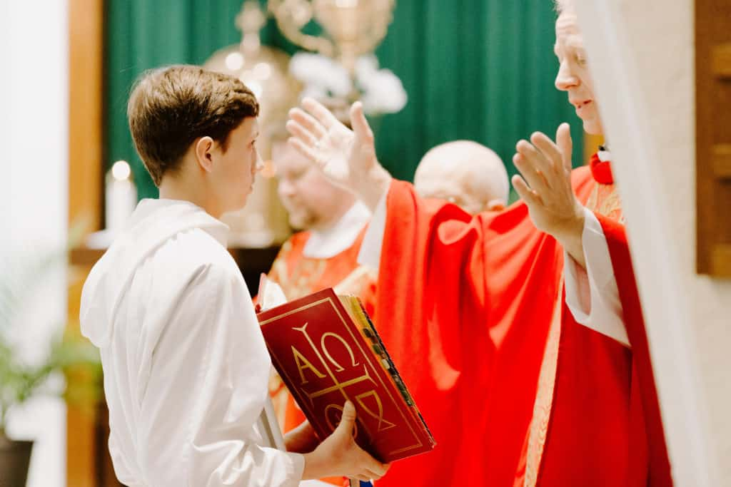 Bishop Bill Wack extends his arms and reads from the Missal during the consecration at the 2019 Confirmation Mass at Little Flower Catholic Church