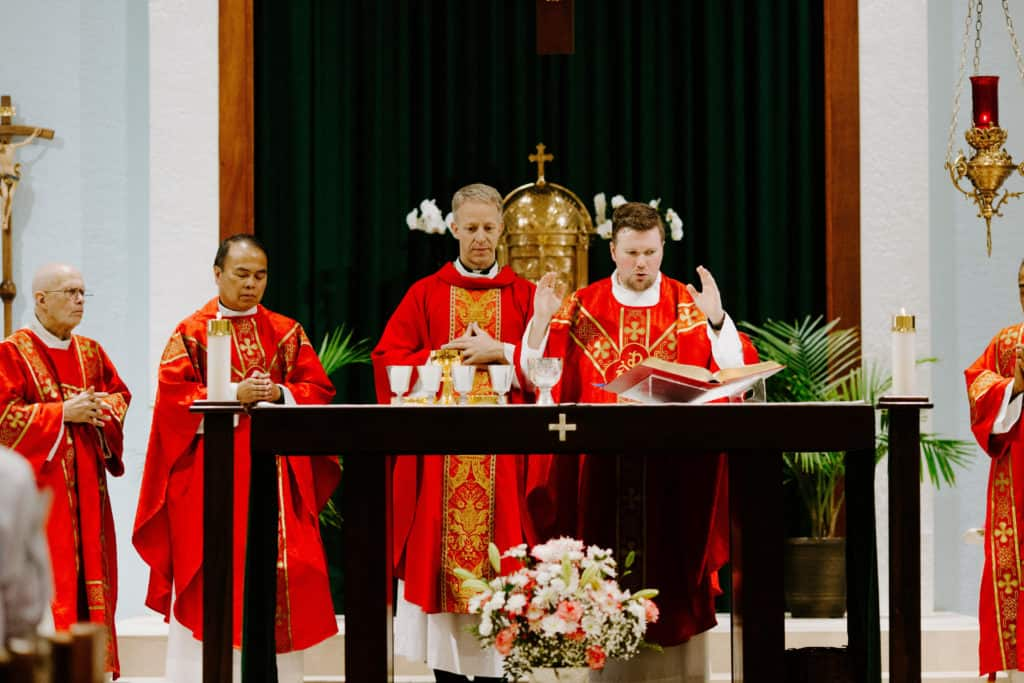 Bishop Bill Wack and Fr. Matt Worthen read from the Missal during the consecration at the 2019 Confirmation Mass at Little Flower Catholic Church