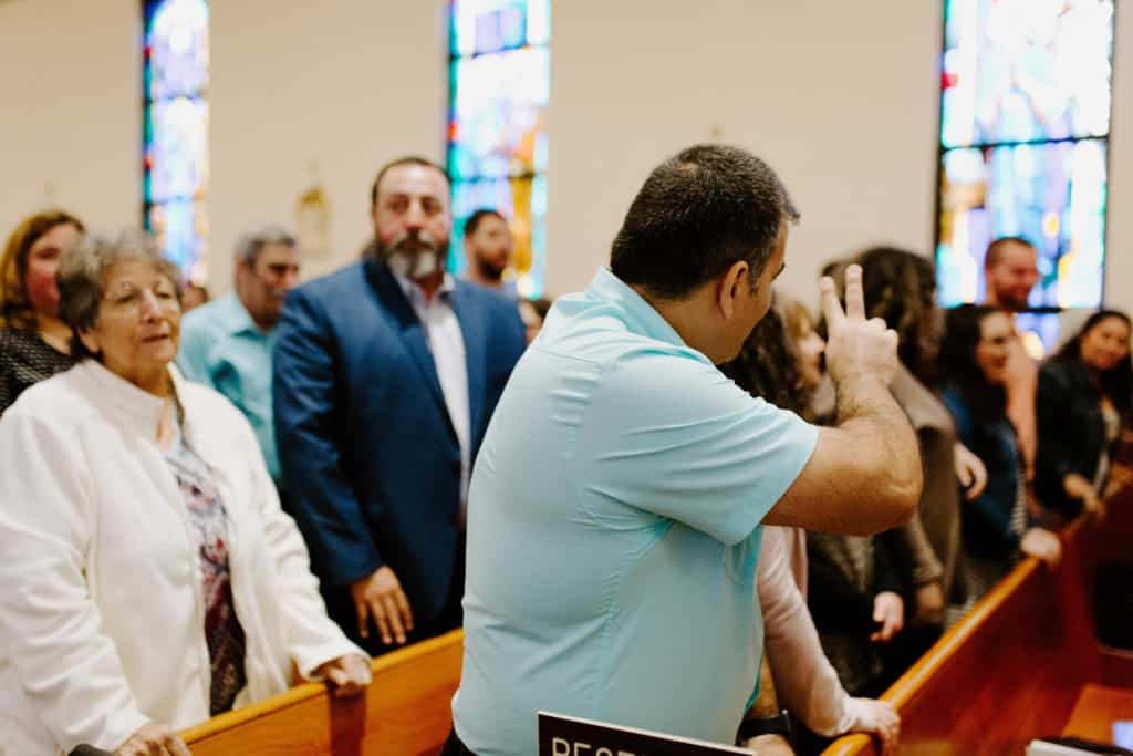 A man in a blue shirt offers peace during the sign of peace at the 2019 Confirmation Mass at Little Flower Catholic Church