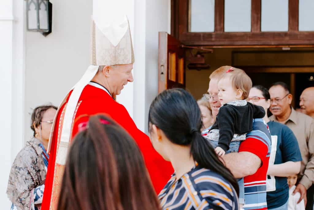 Bishop Bill Wack smiles at a baby after the 2019 Confirmation Mass at Little Flower Catholic Church
