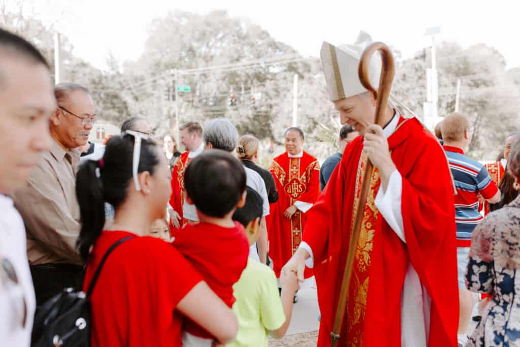 Bishop Bill Wack shakes the hand of a young man after the 2019 Confirmation Mass at Little Flower Catholic Church