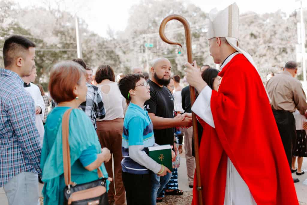 Bishop Bill Wack shakes the hand of a parishioner after the 2019 Confirmation Mass at Little Flower Catholic Church