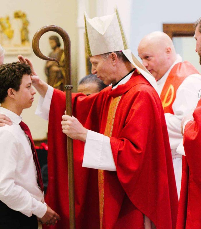 Bishop Bill Wack confirms a high schooler during Mass at Little Flower Catholic Church