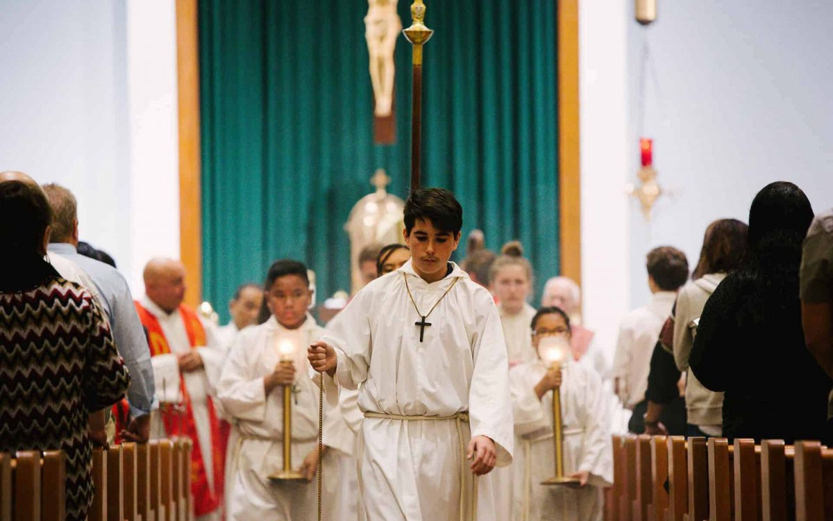 Three altar servers process out at a Mass with Bishop Bill Wack at Little Flower Catholic School