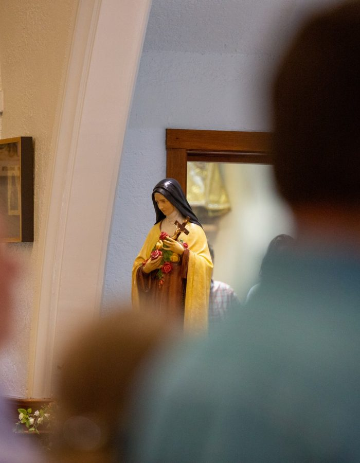 Focus on St. Therese of Lisieux statue between a crowd of parishioners at Little Flower Catholic Church