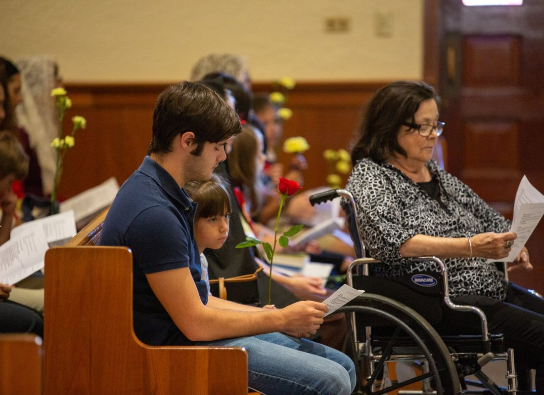 A young man seated in a pew reads the psalm during Mass at Little Flower Catholic Church