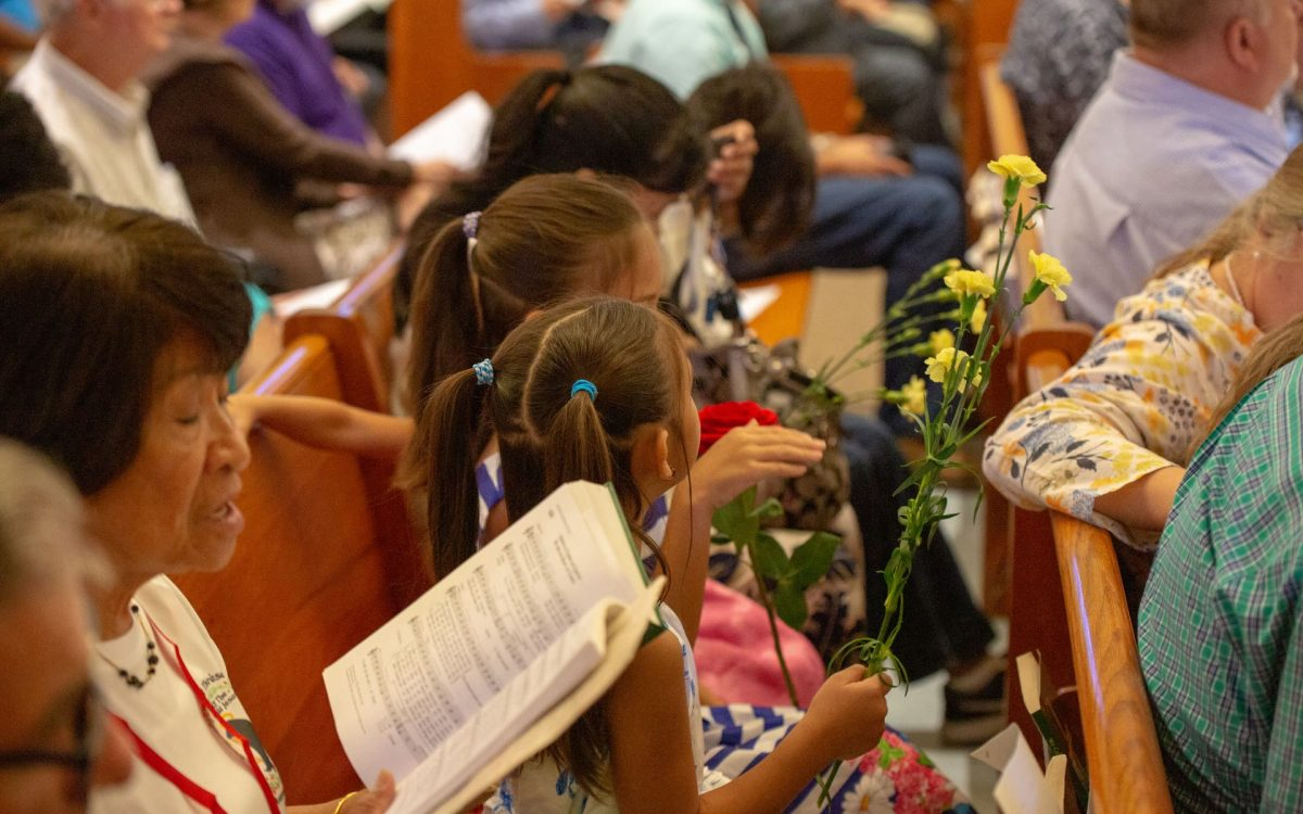 Young children presenting flowers during Mass at Little Flower Catholic Church