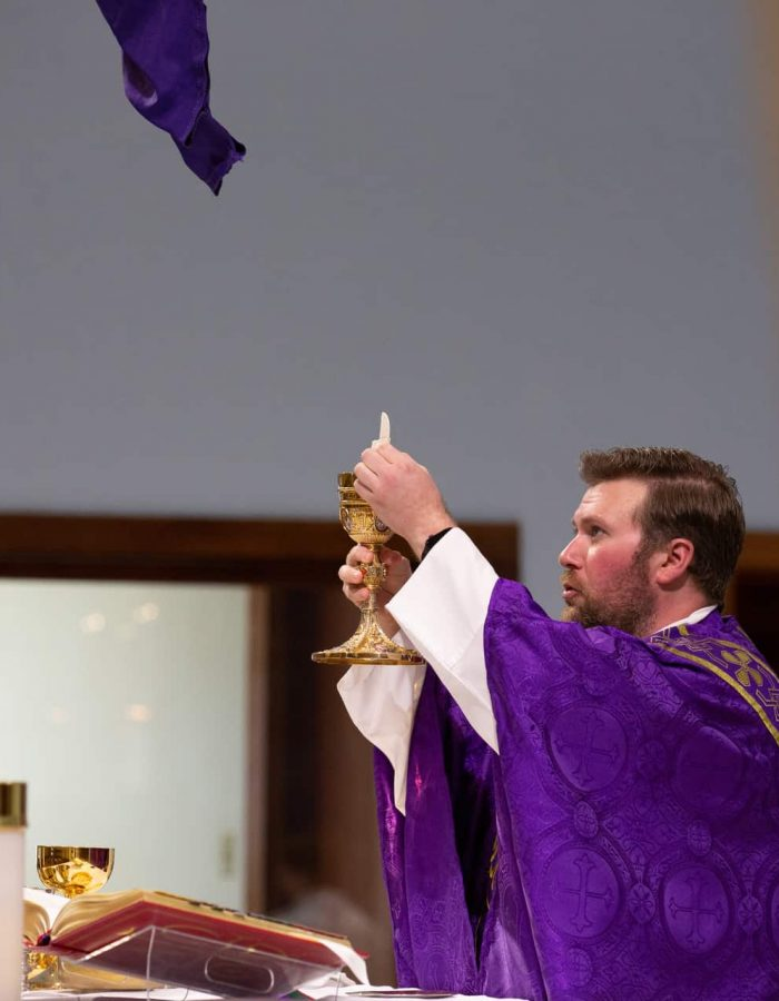 Fr. Matt elevates the host during the consecration at Mass at Little Flower Catholic Church