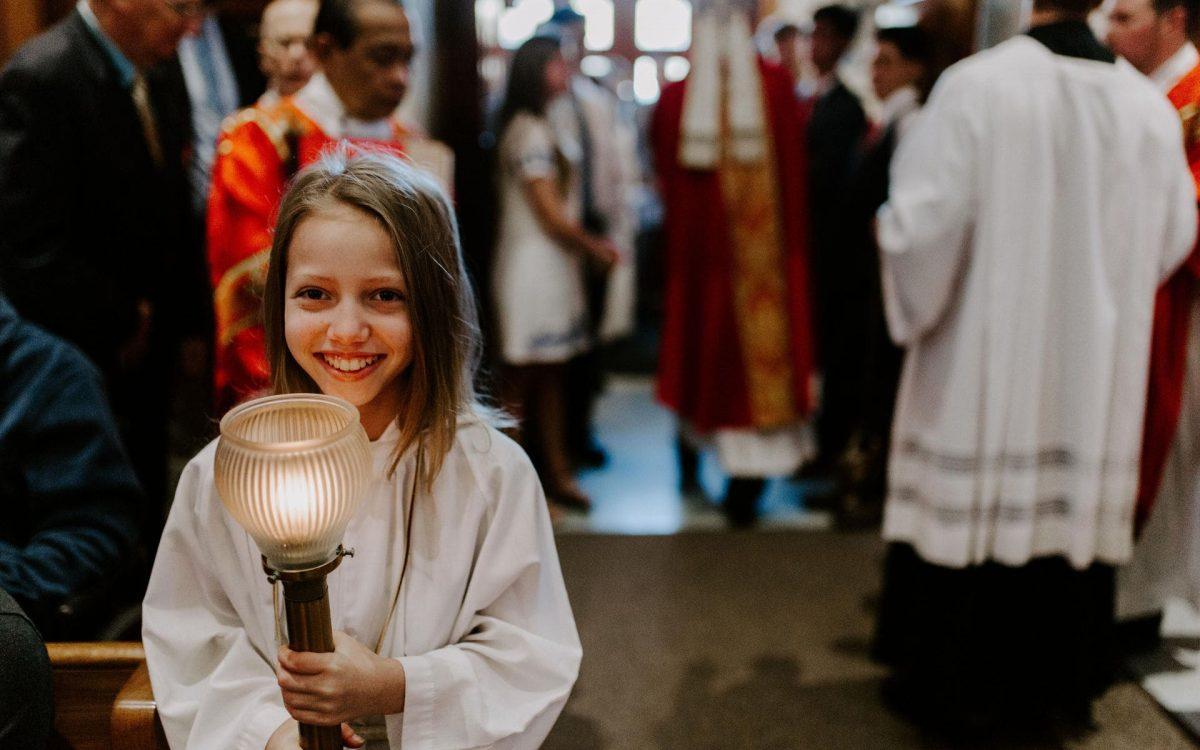 A smiling altar server holding a candle waits to process into Mass at the 2019 Confirmation Mass at Little Flower Catholic Church