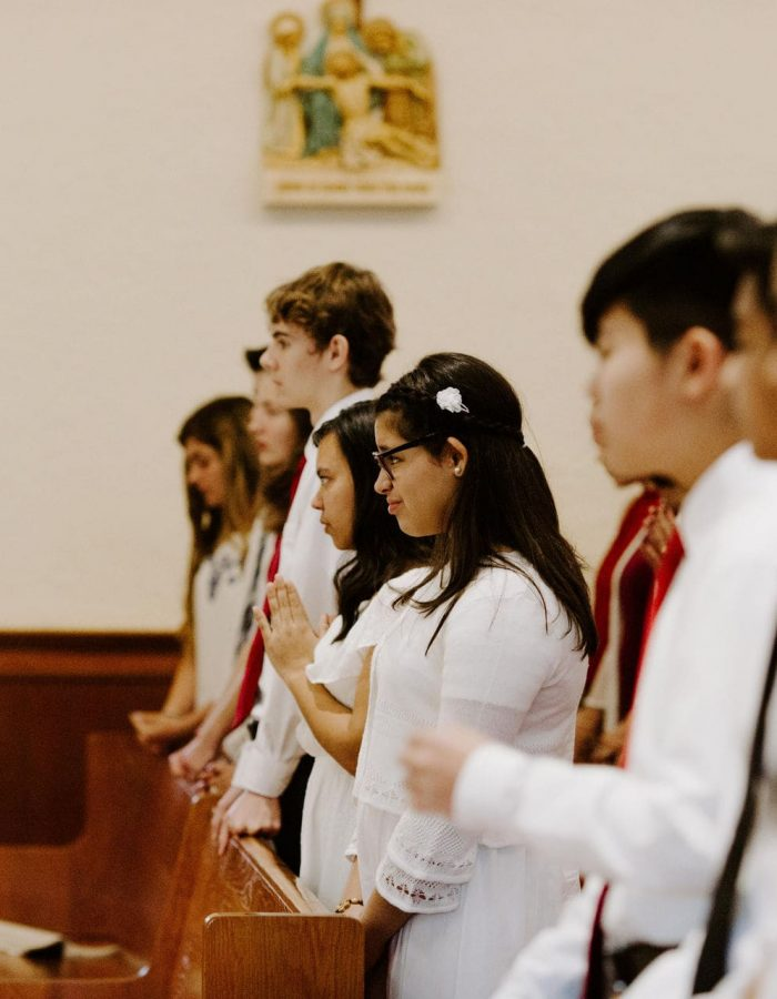Students wearing white pray and prepare for the 2019 Confirmation Mass at Little Flower Catholic Church
