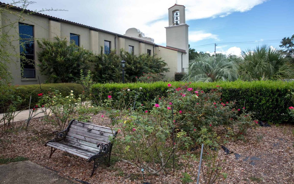 A wooden bench in the rose garden of Little Flower Catholic Church