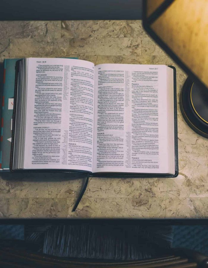 An open bible in front of a lamp