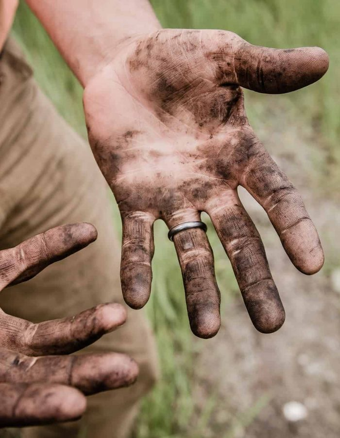 A man with open dirty hands covered in mud