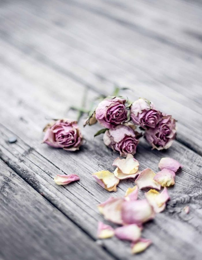 Rose petals sitting on a wooden table